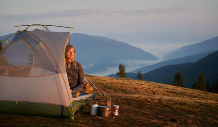 Beautiful woman with interested facial expression watching for stunning mountain scenery from her tent set up on green lawn, next to camping gear. Foggy mountain beskids on the background. Stok Fotoğraf