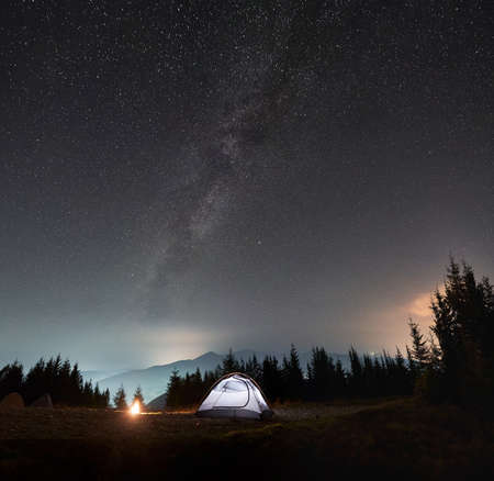 Bright tent near forest and campfire. Cozy place for camping in mountains under shining sky covered with stars and Milky way. Silhouettes of mountain peaks on the background. Stok Fotoğraf