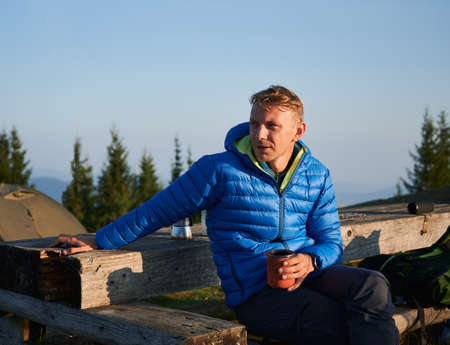 Young man hiker holding cup of coffee and looking aside while sitting on wooden bench in mountains. Male traveler with mug of hot drink in his hand resting outdoors with blue sky on background.