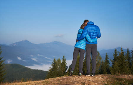 Rear view of couple in love who standing on mountain, watching around beautiful mountain scenery and tenderly embracing each other. Pleasant moment of hugs while walking in the fresh air.