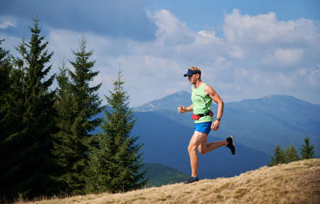 Professional young blond athlete running trail on grassy downhill of mountains in summer sunny day. Beauty mountain landscape on background. Stok Fotoğraf