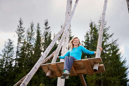 Low angle of beautiful young woman looking at camera and smiling while swinging on wooden swing in coniferous forest. Concept of playfulness, fun and active leisure. Stok Fotoğraf
