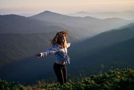 Beautiful joyful woman spreading hands to sides and smiling while enjoying sunny evening in mountains. Happy female traveler wearing flower wreath while standing on grassy hill and rejoicing.