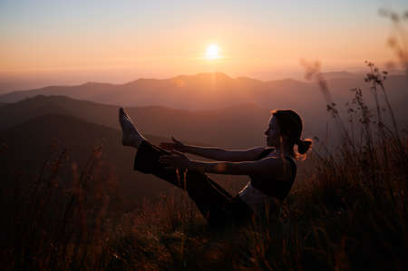Side view of woman practicing yoga in the mountains at sunset. Concept of training outdoor.