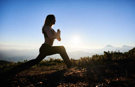 Side view of slim young woman in sportswear doing yoga exercise on grassy hill with blue morning sky on background. Female person doing morning gymnastics outdoors in mountains.