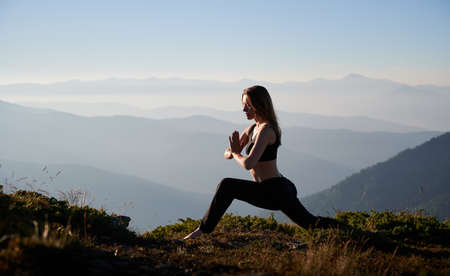 Brunette woman practicing yoga in Warrior pose. Female is meditating outdoor after sunset. Concept of fitness.