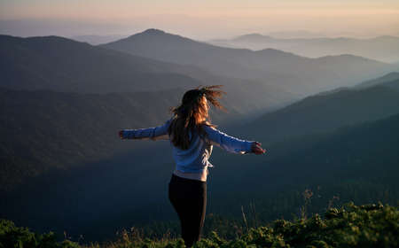 Young slim woman enjoying fresh air and beauty nature in the mountains. Concept of freedom and harmony with nature.