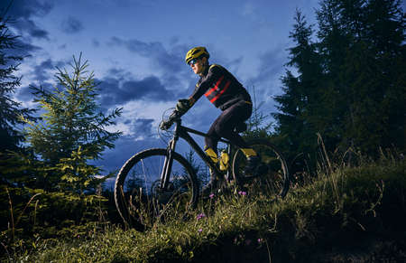 Young man riding bicycle downhill with beautiful blue evening sky on background. Male bicyclist in sports cycling suit cycling down grassy hill at night. Concept of sport, biking and active leisure.