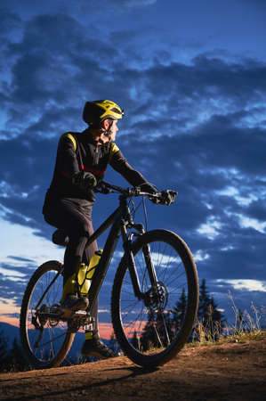 Young man sitting on bicycle under beautiful night sky. Male bicyclist resting on hillside road under blue cloudy sky while riding bicycle in the evening. Concept of sport, biking and active leisure.