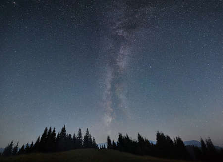 Night sky full of stars, Milky way in the mountains in summer. Galaxy above the hillside, beautiful night scene. Space background. Copy space. Astrophotography