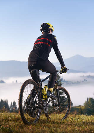 Back view of young man in cycling suit riding bicycle on grassy hill. Male bicyclist enjoying the view of majestic mountains during bicycle ride. Concept of sport and bicycling. Vertical picture.