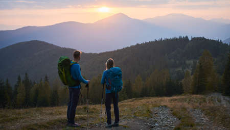 Rear view of lover pair of hikers standing on mountain trail and leaning on trekking sticks watching the mountain scenes in summer evening. Concept of travelling, hiking and active leisure. 版權商用圖片