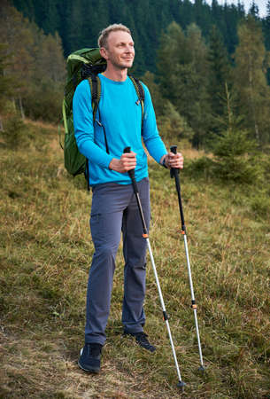 Full length of male hiker with backpack holding trekking poles and smiling while standing on grassy hill. Young happy man traveler enjoying beauty of nature while hiking alone in mountains.