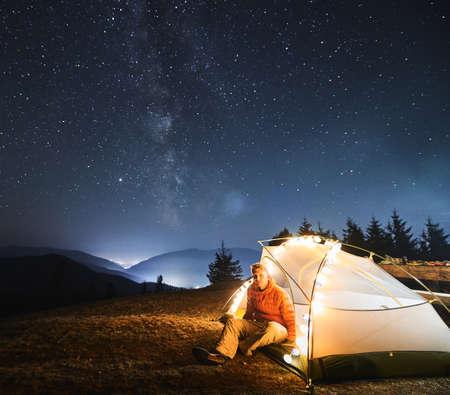 Young traveler sitting in his white tent, lit by light bulbs, on grass under open starry sky with Milky way. Night mountain camping against backdrop of mountain hills and light of city between them.