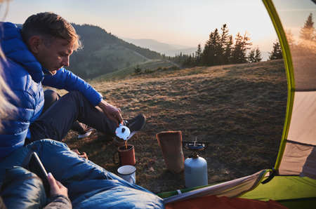 Handsome man traveler sitting on grassy hill near camp tent and pouring hot drink into cup. Male hiker making coffee while woman sitting in tourist tent and holding smartphone. Concept of camping. 版權商用圖片