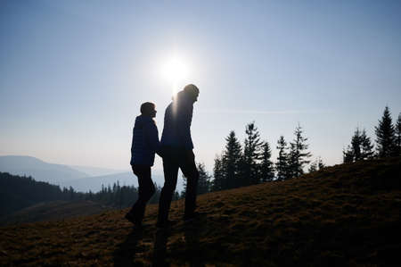 Silhouettes of guy and girl together walking on mountain hill meadow during autumn weekend, on the background of forest and contours of mountain beskids into the distance. 版權商用圖片