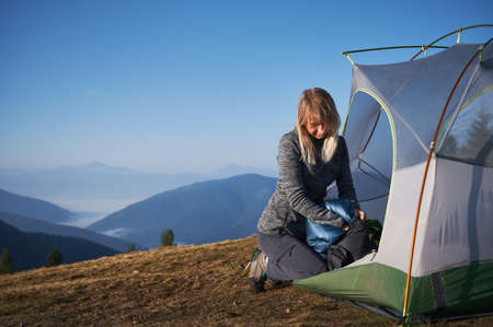 Blonde female traveler packing her sleeping bag in protective bag after nights rest, sitting down at the edge of tent. Vacation in the mountains in tourist campsite. Concept of travelling and camping 版權商用圖片