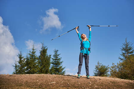 Pleasured female hiker with high up arms in which she holding sticks for walking, closed her eyes and basking in sun, standing on rocky surface in fresh air against blue sky.