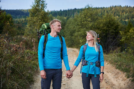 Lover couple of tourists in the same clothes with backpacks walking on dirt road outdoors, holding each others hands. Two hikers walking slowly on trail on the background of green grass and forests. 版權商用圖片