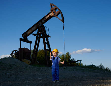 Young child boy in working clothing and helmet with happy face expression standing on stone surface and showing thumb up. Behind him oil pumping machinery in operation under blue sky.