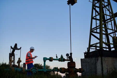 Side view of oil well worker who writing results of pipeline inspection on clipboard. Engineer making notes while servicing the activities of oil rig against blue sky.
