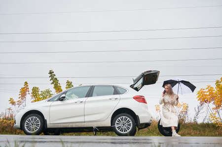 Beautiful woman on road near her white car with punctured car tire. Female driver calling car service for help, holding umbrella, sitting on spare wheel. 版權商用圖片