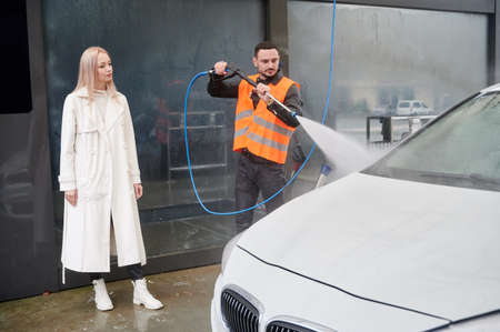 Young man washing car on carwash station, wearing orange vest. Handsome worker cleaning automobile, using high pressure water. Beautiful blonde woman client looking on the white car. 版權商用圖片
