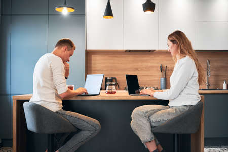 Happy married couple sitting at the wooden table and using modern laptops in modern apartment. Beautiful young woman and man working on notebooks while spending time together at home.