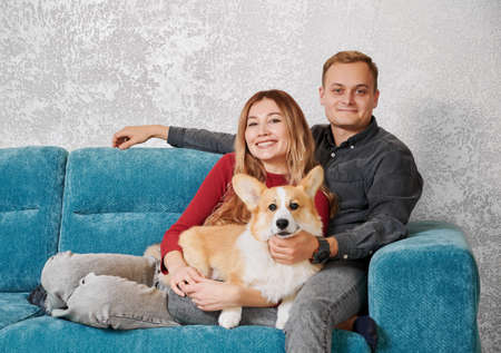 Portrait of cute happy smiling couple sitting on blue sofa and hugging their red-head pet dog on the white sctructural background.