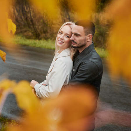 Portrait of young couple in love near the road. Handsome man embracing woman. Smiling girl looking to the camera. View through yellow leaves 版權商用圖片