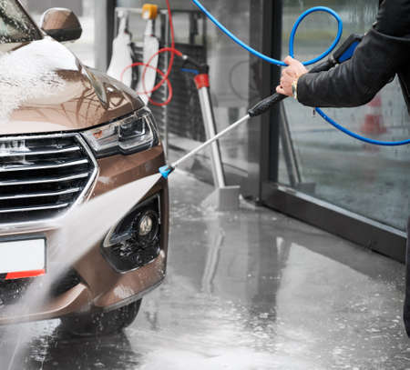 Cropped view of man washing car on carwash station outdoor. Driver cleaning automobile, using high pressure water. 版權商用圖片
