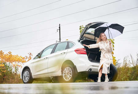 Beautiful woman on road near her stopped white car with punctured car tire. Female driver asking for help, holding umbrella, sitting on spare wheel. 版權商用圖片