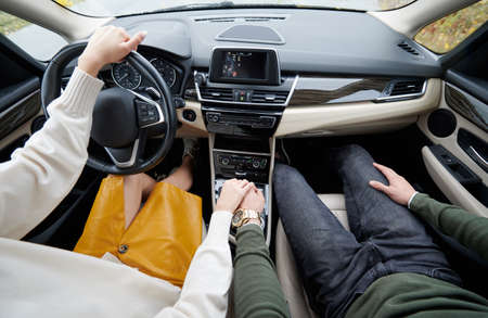 Close up cropped high angle shot of loving couple holding each others hand while driving car on the dashboard background. Concept of romantic automobile trip together.