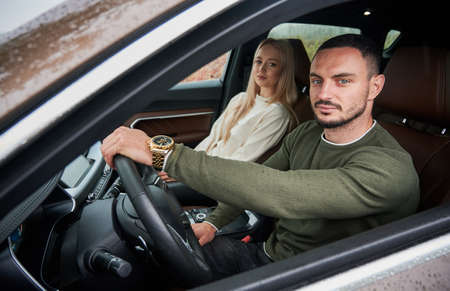 Portrait of serious male driver and beautiful female passenger in front seat of car. Young driver putting his hand on steering wheel, looking into camera through lowered side window.