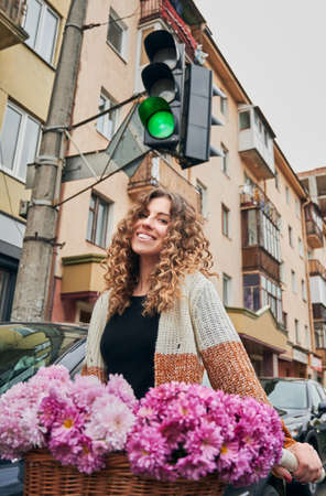 Close up of smiling cute young woman with curly hair riding bicycle with bouquet fresh pink flowers in centre city on traffic light background. Concept of walk on bicycle on city.