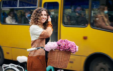 Side view of urly woman travelling by retro bicycle with big basket of pink flowers. Smiling female wearing brown cardigan on bike with chrysanths on handlebar. Concept of city transport.