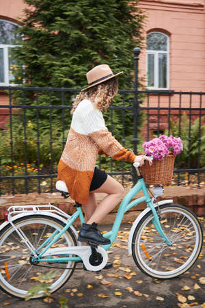 Full length of stylish woman in knitted cardigan riding bicycle with flowers in basket. Charming young woman in hat having bike ride on autumn street.