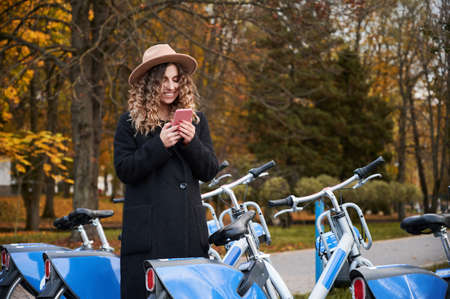 Close up of smiling young woman with curly hair in hat and dressed in black stylish coat standing near modern blue bicycle with phone. Concept of preparing for ride bicycle on urban park. 版權商用圖片