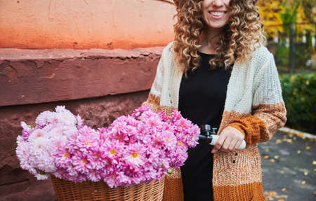 Front view of curly woman posing with bike near corner of brown building. Smiling female wearing brown cardigan is travelling by vintage cycle with big basket of pink camomiles. Concept of activity. 版權商用圖片