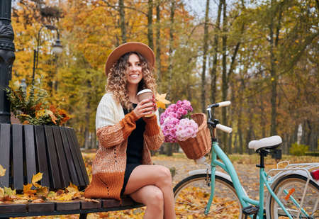 Morning coffee break in city park with bike at autumn. Likable young lady sitting on round bench outdoors with her womens city bicycle admiring autumn landscape. 版權商用圖片