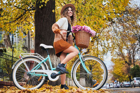 Autumn bike ride through town. Side view of beautiful woman cyclist with curly hair in stylish hat on retro bicycle who stopping near tree on one of city streets during biking in weekend. 版權商用圖片