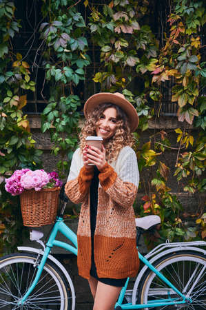 Front view of beautiful young woman holding takeaway cup of coffee and smiling while standing by bicycle with flowers in basket. Elegant woman with coffee to go posing on the street near bike.