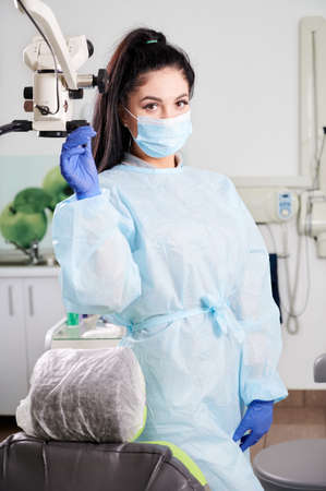 Portrait of a pretty woman dentist, wearing doctors uniform, face mask, gloves standing in her fully equipped dental office. Modern technologies in stomatology. Concept of dentistry and healthcare 版權商用圖片
