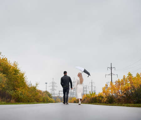 Back view of young couple in love walking on the road under cloudy sky with rain. Man and woman holding hands. Low angle view