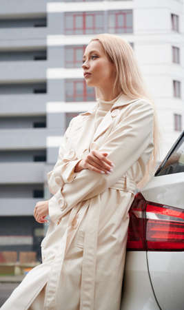 Portrait of beautiful young woman posing near her white car outdoor.