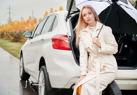 Portrait of attractive blonde business lady sitting on spare tire, holding umbrella from the rain. On the background white car with open trunk and yellow autumn roadside bushes. 版權商用圖片