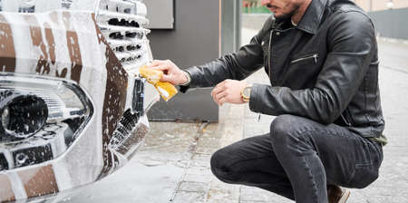 Young man washing car on carwash station outdoor. Handsome worker cleaning automobile, using sponge and soap.