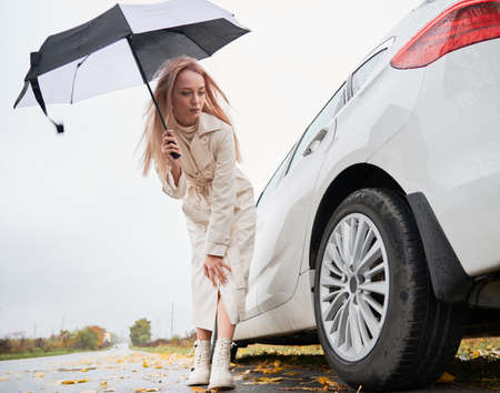 Beautiful woman on a road stopped her white car with punctured car tire. Female driver looking on tyre, holding umbrella.