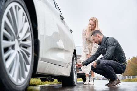 Beautiful young woman standing by automobile and smiling while man checking wheel. Handsome auto mechanic helping female driver to change car tire on the road.