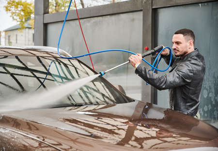 Guy washing dirt from windshield of his auto, using powerful stream of water. Rinsing machine by pressure water with aquatic gun after soaping at self-service car wash station.